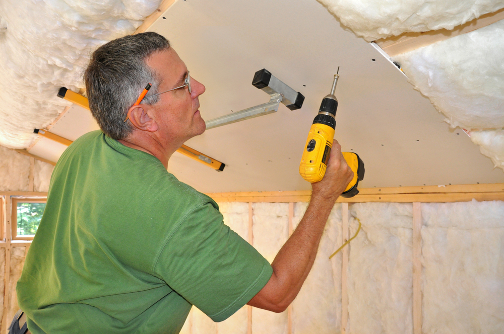 man attaching drywall on ceiling